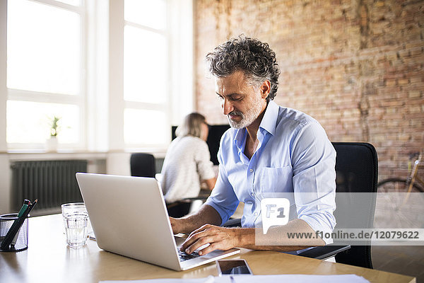 Geschäftsmann mit Laptop im Büro mit Kollegen im Hintergrund
