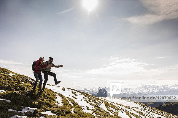 Deutschland  Bayern  Oberstdorf  zwei Wanderer  die auf der Alm springen