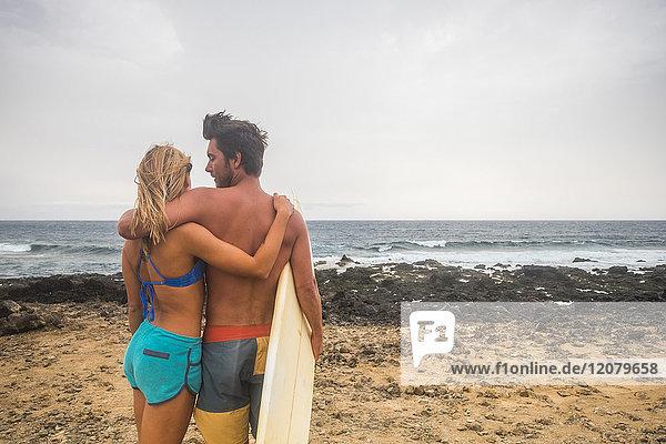 Junges Paar mit Surfbrett am Strand stehend