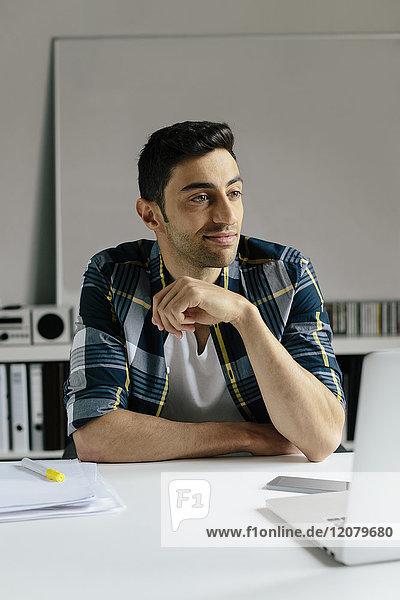 Junger Mann mit Laptop am Schreibtisch im Büro