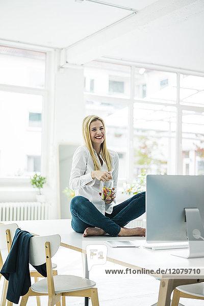 Glückliche Geschäftsfrau sitzt auf dem Schreibtisch im Büro