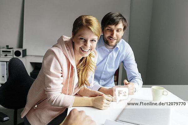 Porträt der glücklichen Kollegen am Schreibtisch im Büro