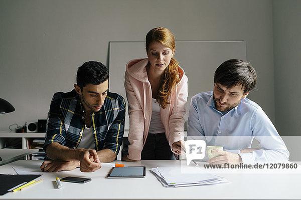 Drei Kollegen arbeiten zusammen am Schreibtisch im Büro
