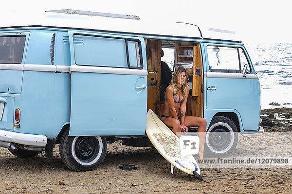 Porträt einer glücklichen jungen Frau mit Surfbrett im Van am Strand