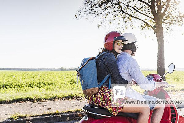 Fröhliches junges Paar auf dem Motorroller mit Rucksack auf dem Rücken