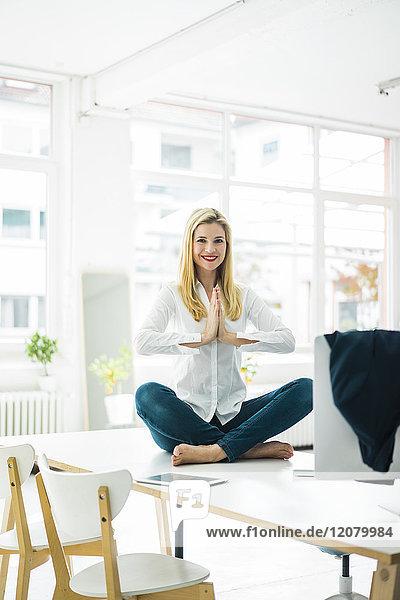 Lächelnde Geschäftsfrau sitzt auf dem Schreibtisch im Büro und übt Yoga.