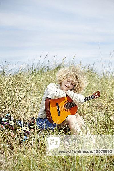 Porträt einer jungen Frau mit Gitarre  die sich in Stranddünen entspannt.