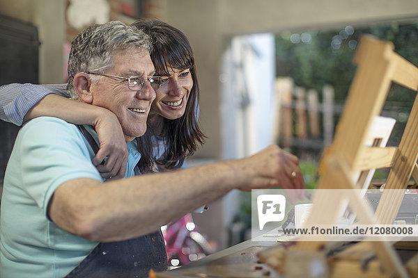 Smiling woman embracing senior man painting