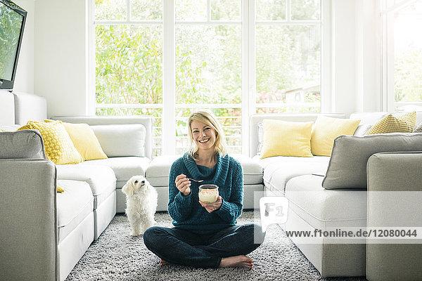Porträt einer glücklichen Frau mit einem Hund  der Fruchtjoghurt im Wohnzimmer isst.