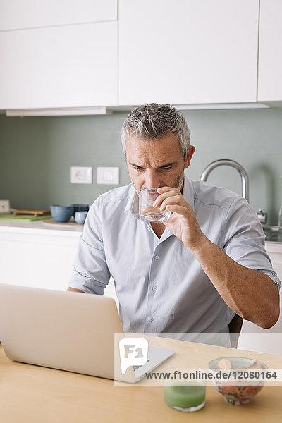 Mann trinkt Wasser aus Glas und nutzt Laptop im Home-Office