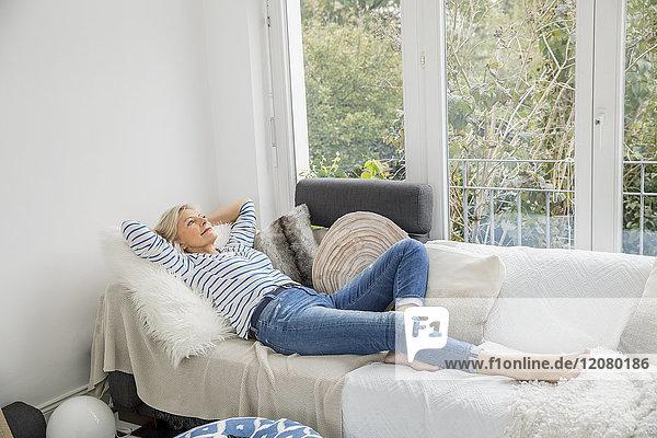 Lächelnde Seniorin entspannt auf der Couch im Wohnzimmer