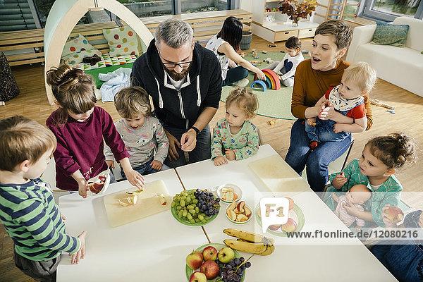 Gruppe von Kindern und Lehrern  die im Kindergarten Obst zubereiten