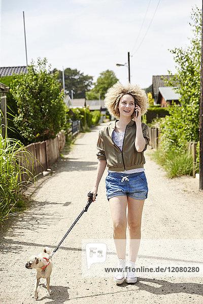 Junge blonde Frau am Telefon geht mit ihrem Hund spazieren.