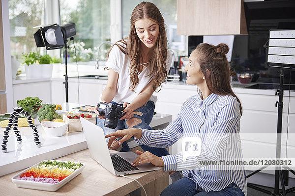 Zwei Food-Blogger mit Laptop und Kamera in der Küche