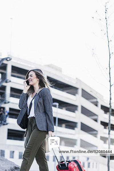 Glückliche junge Frau mit Rollkoffer am Handy in der Stadt