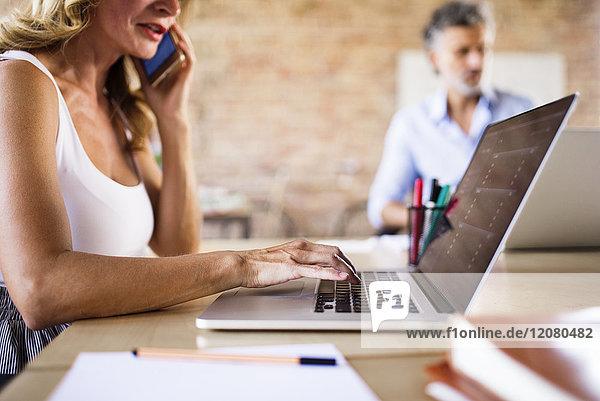 Geschäftsfrau mit Handy und Laptop am Schreibtisch im Büro