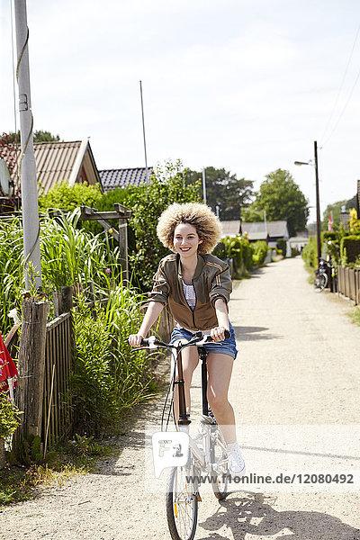 Porträt einer lächelnden jungen Frau auf dem Fahrrad