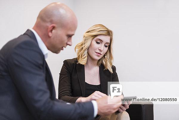 Geschäftsmann und Geschäftsfrau sitzen auf der Couch und teilen sich ein Tablett.
