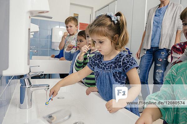 Kinder beim Zähneputzen im Bad eines Kindergartens