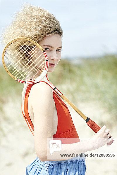 Portrait der jungen Frau mit Tennisschläger am Strand
