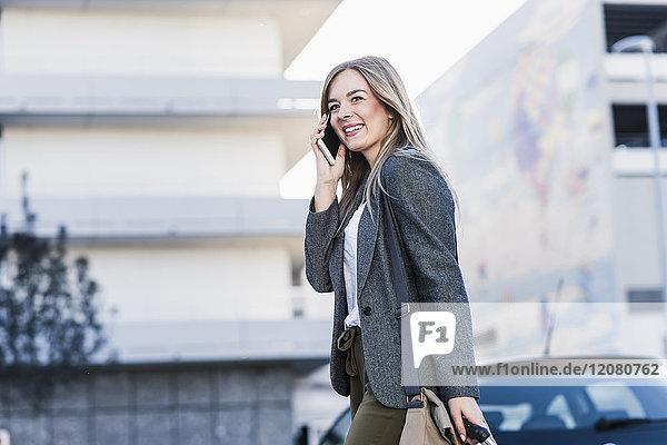 Glückliche junge Frau am Handy in der Stadt