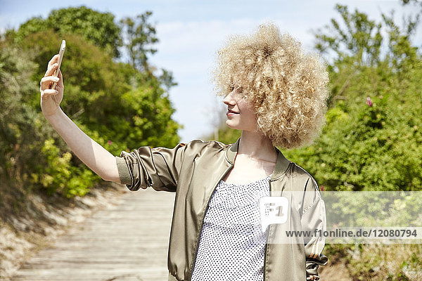 Junge blonde Frau nimmt Selfie mit Smartphone