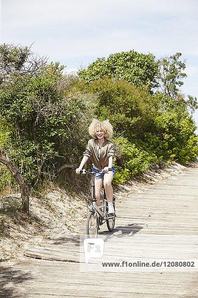 Glückliche junge Frau beim Fahrradfahren