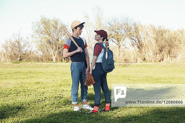 Junges Paar mit Baseballausrüstung im Park