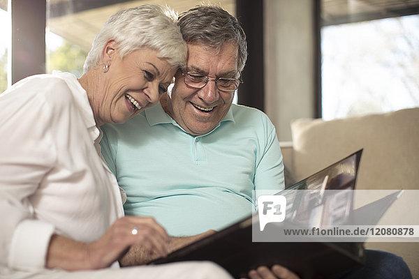 Fröhliches Seniorenpaar auf der Couch beim Betrachten des Fotoalbums