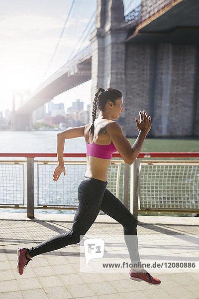 Frau macht morgens Dehnübungen in Manhattan bei der Brooklyn Bridge.