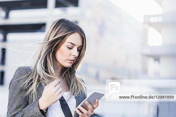 Seriöse junge Frau beim Telefonieren im Freien