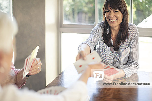 Seniorenpaar spielt Karten mit Tochter zu Hause