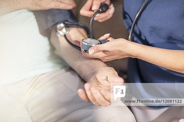 Krankenschwester  die den Blutdruck eines älteren Patienten zu Hause misst.