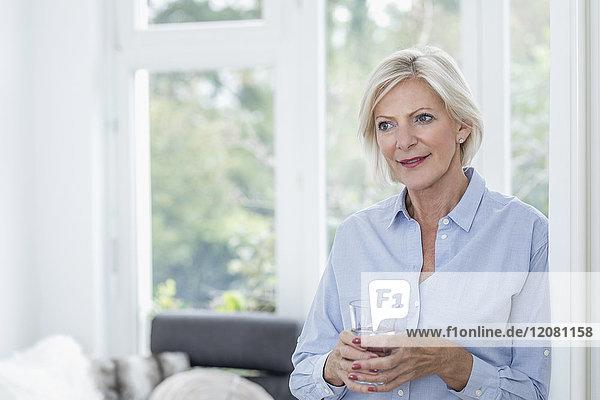 Porträt einer lächelnden Seniorin mit einem Glas Wasser im Wohnzimmer