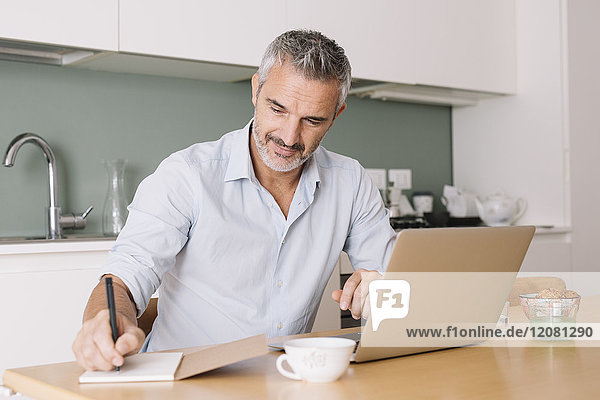 Smiling man writing in notebook and using laptop in home office