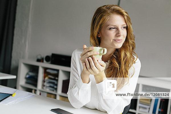 Lächelnde junge Frau mit Tasse Kaffee am Schreibtisch im Büro