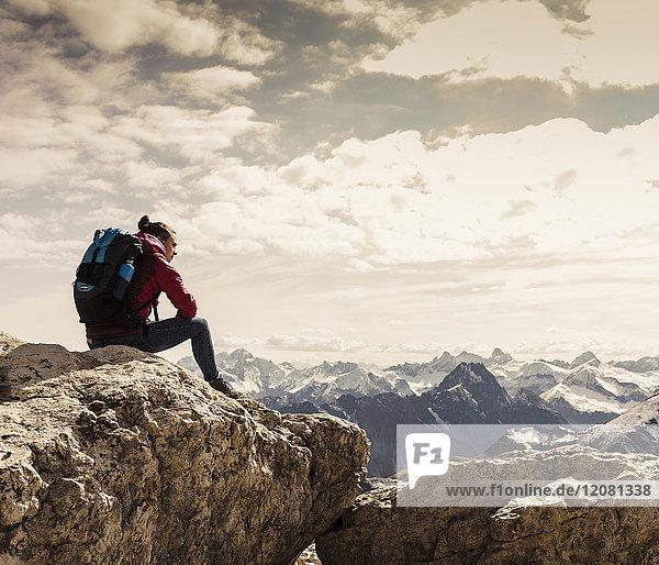 Deutschland,  Bayern,  Oberstdorf,  Frau auf Felsen sitzend in alpiner Landschaft