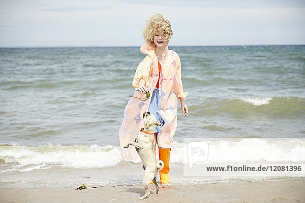 Lächelnde junge Frau spielt mit ihrem Hund am Strand