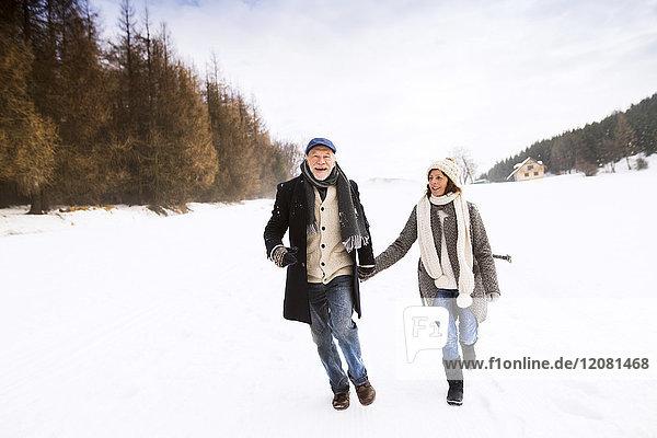 Glückliches Seniorenpaar beim Wandern in verschneiter Landschaft