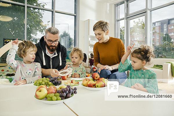 Kinder und Lehrer  die im Kindergarten Obst zubereiten