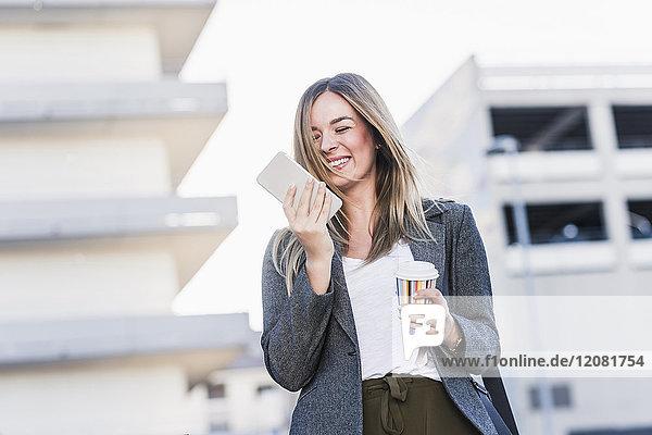 Glückliche junge Frau mit Kaffee zum Mitnehmen und Handy in der Stadt