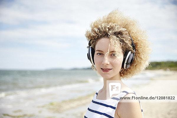 Portrait einer jungen blonden Frau mit Kopfhörer am Strand