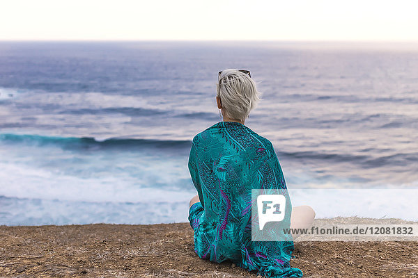Indonesia  Lombok  woman sitting at the coast looking at view