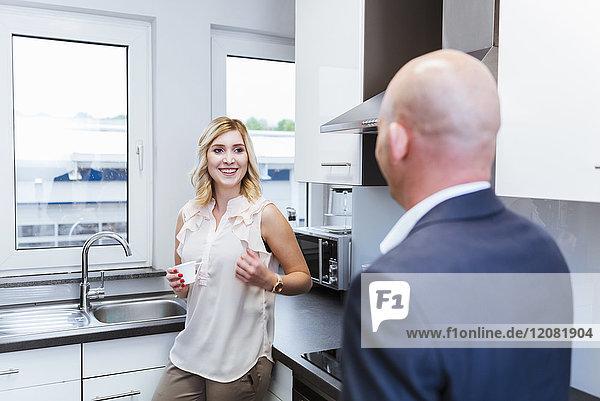 Geschäftsmann und Geschäftsfrau bei Kaffeepause in der Küche