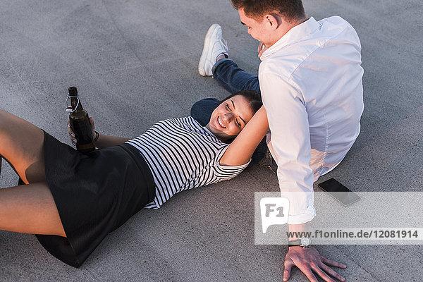 Ein glückliches junges Paar entspannt sich bei Sonnenuntergang im Freien