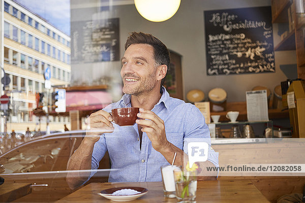 Portrait of laghing man with cup of coffee in a coffee shop
