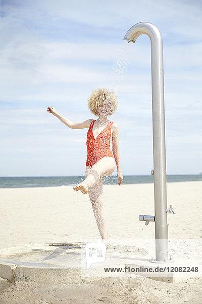 Junge Frau blonde Frau beim Duschen am Strand