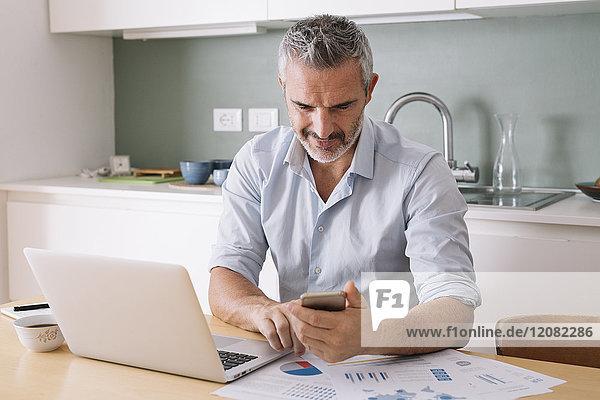 Mann analysiert Daten und nutzt Laptop und Handy im Home-Office