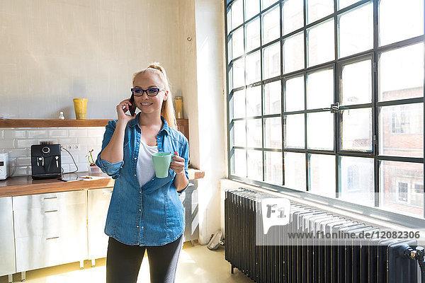 Porträt einer lächelnden Geschäftsfrau am Telefon stehend mit Kaffeetasse in der Küche