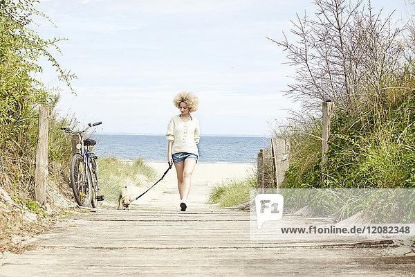 Junge Frau geht mit ihrem Hund spazieren.